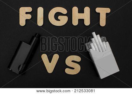 Cigarettes against Vape. Electronic cigarette over a dark background. E-cigarette for vaping. Popular devices of the year - modern vaping device. Stop smoking,start vaping vape.