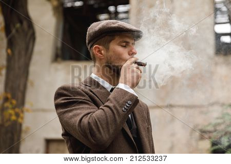 A man in a brown suit and hat stands on the street near an abandoned building and enjoys smoking cigars. Retro. Outdoors.