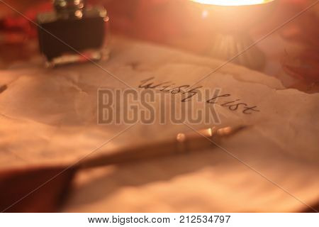 Old wishlist with feather pen and ink and candle on wooden table. Christmas feeling.