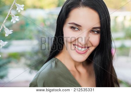 Portrait of beautiful smiling young woman against green nature with flowers. Concept of atractive healthy woman