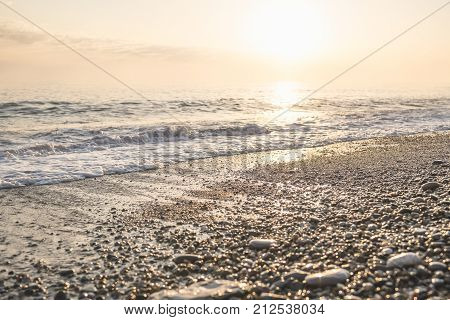 Horizontal shot of the sunset on sea in Sunny summer evening the sun in the frame shining and reflecting in the water wet pebbles on the coast glistens in the sun