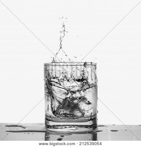 Cutout Ice cubes splashing into glass of water isolated on white background