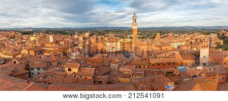 Panoramic aerial view of Mangia Tower or Torre del Mangia towering above of the Palazzo Pubblico on Piazza del Campo in medieval city of Siena in the cloudy day, Tuscany, Italy poster
