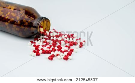 Colorful of antibiotic capsules pills with amber glass bottle on white background. Drug resistance antibiotic drug use with reasonable health policy and health insurance concept.