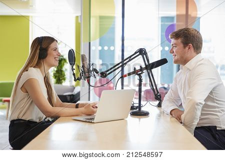 Young woman interviewing a guest in a studio for a podcast
