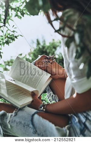 What is going to happen next? Close-up of young woman holding an open book while spending time outdoors