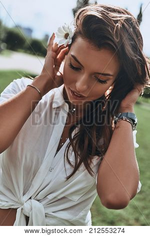 Naturally beautiful. Attractive young smiling woman keeping flower in hair and looking down while spending carefree time outdoors