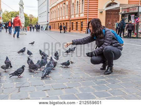 Brasov Romania October 06 2017 : Young woman feeding pigeons outdoors in the Old city of Brasov in Romania
