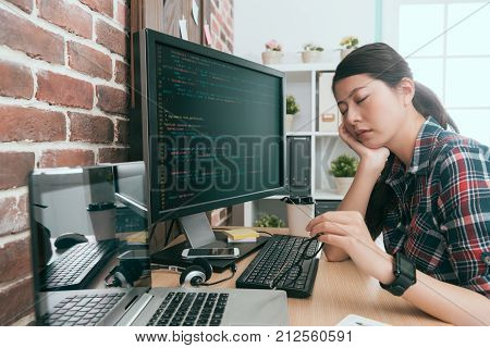 Developer Sitting In Front Of Working Computer
