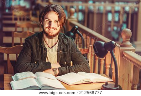 Portrait of smiling young bearded student man reading in a library hall on table with lot of books and lamp, indoor dusk time, education concept