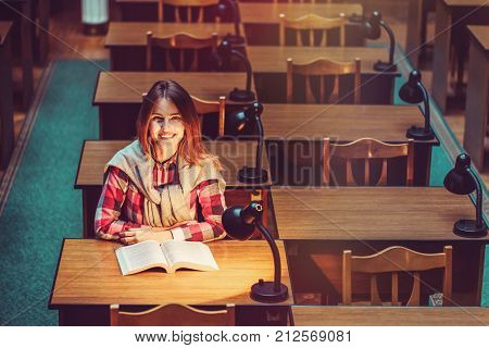 Successful casual stylish student girl wears glasses read book in reading hall in the library, education concept