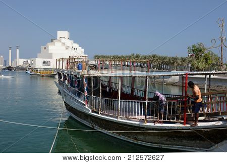 DOHA, QATAR - NOVEMBER 6, 2017: Men at work on the superstructure of a dhow, with  the Museum of Islamic Art beyond
