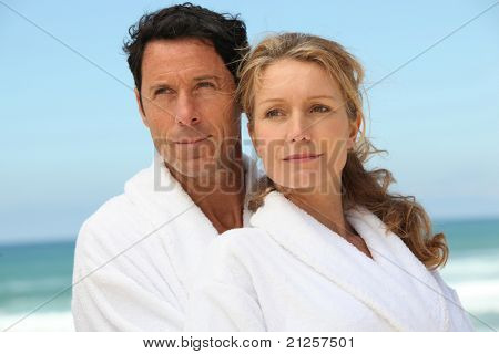Couple on the beach in white dressing downs