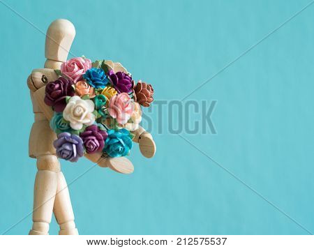 select focus of wooden puppet. The wooden puppet holds flower and standing on the wood table. the background is blue and copy space for text