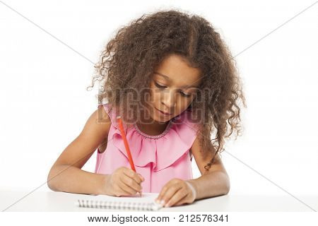 Education. Close up portrait of African American little girl is sitting at the table with a notebook for drawing, isolated on white background