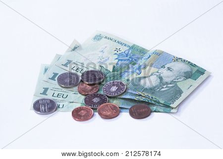 Four Banknotes Worth  1 Romanian Leu With Several Coins Worth 10 And 5 Romanian Bani Isolated On A W