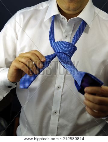 Tie a tie. Corporation career and business concept - close up of man in white shirt adjusting blue cravat on neck.