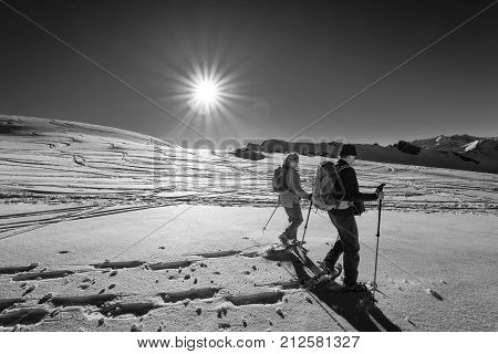 Mature couple hiking with snowshoes in winter mountain landscape at sunset. Alps, Germany, Bavaria, Allgau.