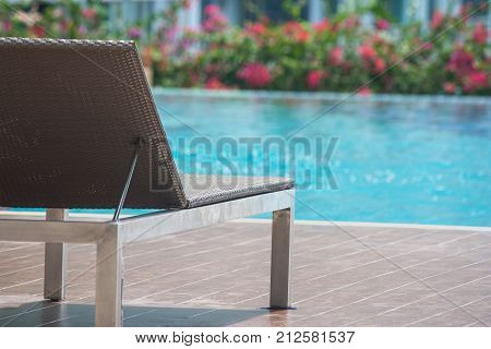 Close up daybed setting on wooden floor beside swimming pool at outside the resort. (Selective focus)