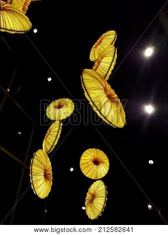 Yellow bright lampshades hanging from the ceiling in the dark