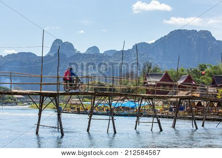 Vang Vieng, Laos - January 19, 2017: Wooden bridge across Nam Song river at Vang Vieng, Laos