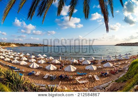 Tourists Relaxing On The Beach In The Summer Vacation. Peyia Village Paphos District Cyprus.
