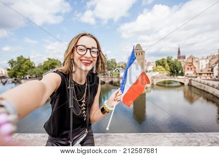 Portrait of a young woman tourist with french flag on the beautiful landscape background with river and towers in the old town of Strassbourg city, France