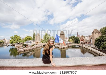 Young woman tourist sitting back with french flag on the beautiful landscape background with river and towers in the old town of Strassbourg city, France