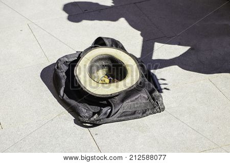 A hat with coins lies on the asphalt in the shadow of a street guitarist waiting for awards for music.