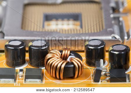 Capacitors with chips on the board close up. The details of the motherboard on the background of the space for the processor.
