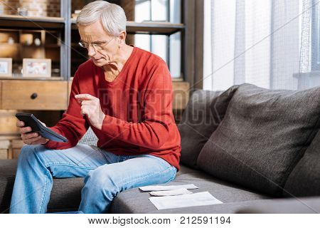 Daily expenses. Serious smart aged man sitting on the sofa and holding a calculator while counting his daily expenses