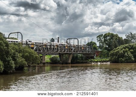 Parramatta Australia - March 24 2017: Train rides over train bridge crossing the Parramatta River approaching the city under heavy cloudscape. Green belt along shores.