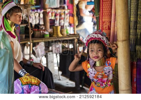 CHIANG RAI, THAILAND - NOVEMBER 4 2017: Unidentified Long Neck Karen hill tribe girl smiling and showing victory sign