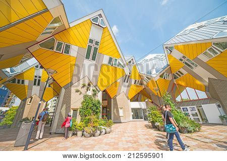 ROTTERDAM HOLLAND - AUGUST 22 2017; Cube houses of Rotterdam a quirky bright yellow architecturally unusual angular cube shape apartment block focus on structure with few tourists showing interest in the unusual.