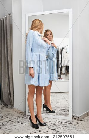 Young beautiful woman wearing a new dress looking in the mirror while shopping for new clothes at the local boutique fashion style seasonal beauty glamorous lifestyle wellbeing teenager consumerism.