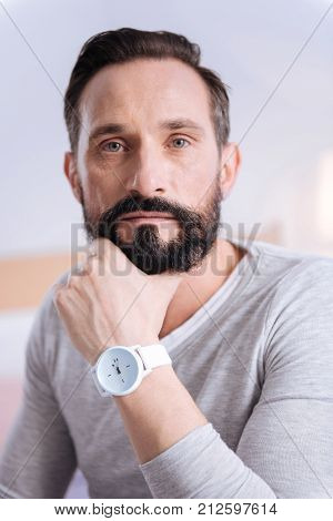 Considering things. Serious bearded dark-haired wrinkled man of middle age wearing a white shirt and a watch and touching his chin while thinking
