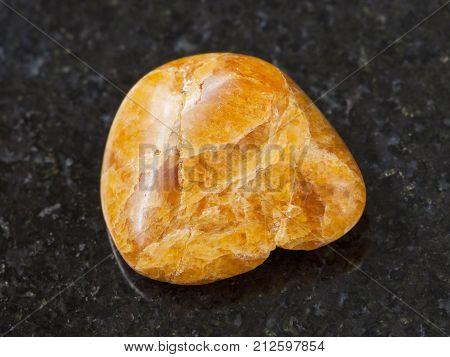 Tumbled Clinohumite Gemstone On Dark Background
