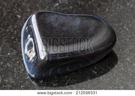 Tumbled Hawk-eye Gemstone On Dark Background