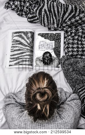 trendy hipster woman lying in her bed and reading a fashion magazine on a cozy sunday