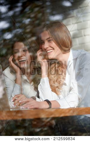 Beautiful young female friends smiling cheerfully while browsing something together on the laptop relaxing at the coffee shop friendship people living urban lifestyle teenagers campus technology 3g.
