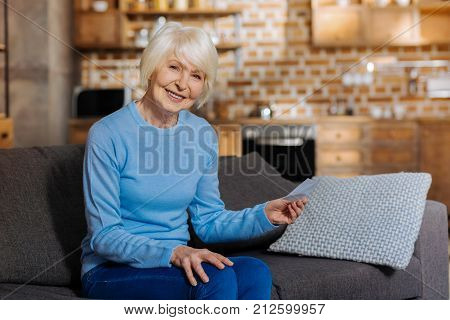 Baby boomer. Delighted nice aged woman holding a note and smiling while being in a positive mood