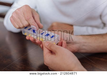 Pill box. Progressive smart pensioner using a special convenient pill box while recovering at home