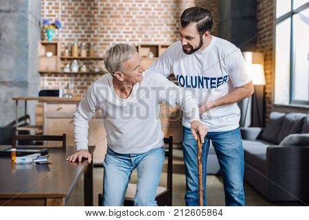 Support. Young reliable social worker looking attentive and careful while helping an old man to stand up and walk