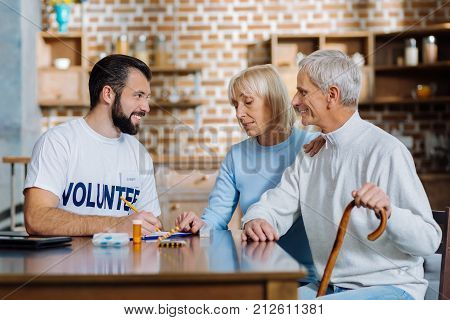 Valuable advice. Cheerful polite reliable social worker smiling to lovely pensioners while recommending them a new treatment