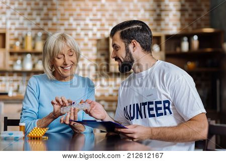 Take one. Cheerful positive senior woman looking happy while sitting with her social worker and taking a little useful pill from a very convenient pill box