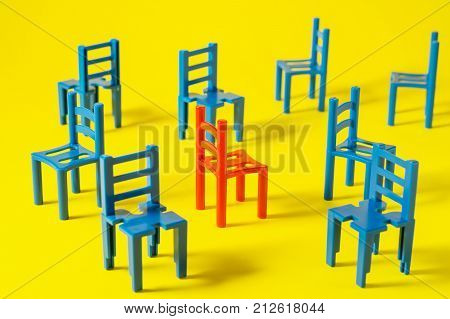 Unique red chair in a group blue others. Leadership concept. Empty chairs on yellow background. The concept of uniqueness distinction from others.