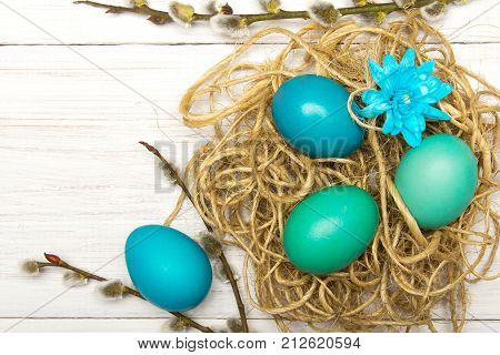 Easter background with eggs nest and catkins on white wooden background copy space