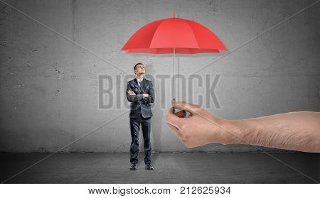 A small businessman stands looking up on a red open umbrella offered by a giant male hand. Unexpected assistance. Business support. Corporate insurance.