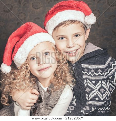 Funny kids sitting near the Christmas tree. Wearing santa hats. They are looking at the camera, smiling. Waiting for Cristmas. New Year.