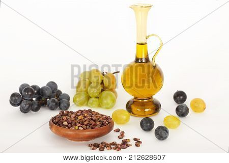 Healing grape seeds oil in a glass jar, fresh grapes on white background. Grape seed extract.